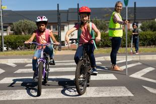 deux enfants apprenant à faire du vélo à l'école